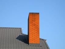 Tubo arancione del mattone, tetto nero, cielo blu, Fotografie Stock