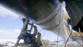 Tubo d'acciaio della condotta della saldatura del lavoratore dell'industria utilizzando la torcia del metallo nel giorno di inver stock footage