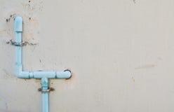 Tubo de agua azul en la pared del cemento Foto de archivo