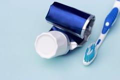 Tubo de dentífrico vazio e de escova de dentes no fundo azul imagem de stock