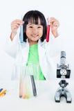 Tubo de ensaio de exame da menina chinesa asiática feliz com uniforme imagem de stock royalty free