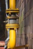 Tubo de gas amarillo con el grifo en la pared marrón Fotos de archivo libres de regalías