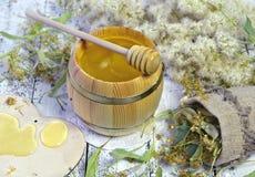 Tubo de la miel, del cazo, de las flores del tilo y del bolso de arpillera en tablones de madera Imágenes de archivo libres de regalías