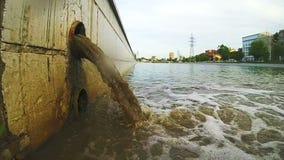 Tubo de las aguas residuales que descarga en el río El dren lleva las aguas residuales almacen de metraje de vídeo