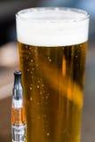 Tubo de Vape al lado de la cerveza imagen de archivo libre de regalías