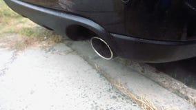 Tubo del coche que emite los gas de escape metrajes