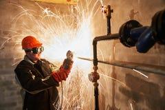 Tubo del corte del trabajador con las chispas por el cortador de la antorcha de la llama de la amoladora Fotografía de archivo