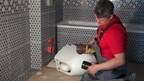 Tubo del corte del hombre del fontanero con la amoladora de ángulo para la taza del inodoro colgante almacen de video