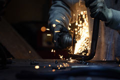 Tubo del metallo di taglio del lavoratore facendo uso della macchina per la frantumazione angolare Fotografia Stock