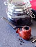 Tubo dell'incastonatore con la ciotola di rovo del grano del birdseye e un barattolo di tabacco sciolto Immagine Stock