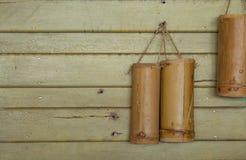 Tubo di bambù per acqua potabile Appendendo su una parete di legno immagini stock libere da diritti