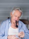 Tubo di fumo dell'uomo anziano Fotografia Stock Libera da Diritti