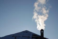 Tubo di fumo su un tetto nevoso Immagini Stock