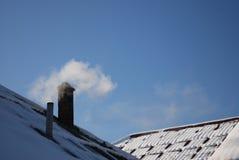Tubo di fumo su un tetto nevoso Fotografia Stock Libera da Diritti