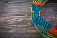 Tubo di gomma di spruzzatura del giardino della mano sul conce di legno di agricoltura del bordo Fotografia Stock