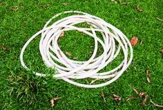 Tubo di gomma sul campo di erba verde Fotografie Stock Libere da Diritti