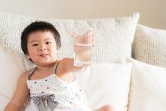 Tubo di livello bevente e La della piccola della ragazza tenuta asiatica felice della mano fotografie stock