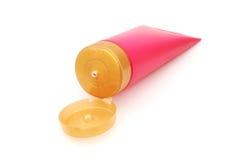 Tubo di plastica rosa con il coperchio giallo aperto del cappuccio Fotografie Stock