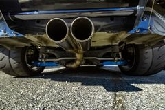 Tubo di scarico di Chrome al fondo dell'automobile con le viste di molto largamente Fotografia Stock