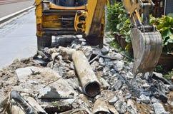 Tubo di scavatura del cemento amianto dell'escavatore a cucchiaia rovescia. Fotografia Stock