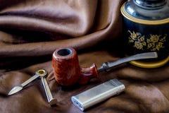 Tubo e humidor su seta marrone Fotografie Stock