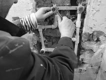 Tubo e portoni del propilene in un muro di mattoni - saldatura del propilene immagine stock