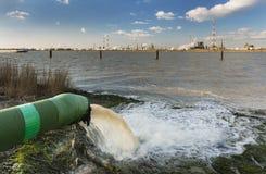 Tubo e raffineria dell'acqua di scarico al fiume Fotografia Stock