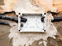 Tubo elettrico del condotto della bobina sulla scatola incastonata in parete fotografia stock