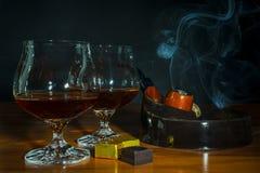 Tubo escocés de bebida y de tabaco con humo en fondo negro Imagen de archivo libre de regalías
