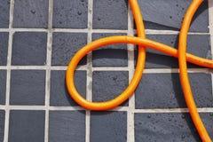 Tubo flessibile arrotolato sulle mattonelle   Fotografie Stock Libere da Diritti