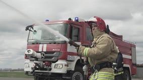 Tubo flessibile dell'acqua della tenuta del pompiere vicino al camion con attrezzatura archivi video