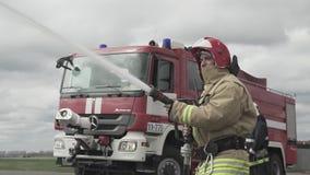 Tubo flessibile dell'acqua della tenuta del pompiere vicino al camion con attrezzatura video d archivio