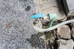Tubo flessibile di giardino o tubo di gomma bianco con il rubinetto su erba fotografia stock