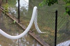 Tubo flessibile di plastica dell'acqua del grande diametro collegato alla forte pompa idraulica sopra il recinto di filo metallic immagini stock libere da diritti