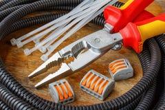 Tubo ondulato di plastica per il cablaggio con le pinze di combinazione ed il terminale filo a scatto rapido sulla tavola di legn fotografia stock