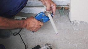Tubo plástico del metal de los cortes del fontanero con un cortador de tubo Tijeras para un corte plástico del tubo Concepto de l almacen de video