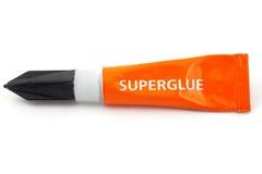 Tubo plástico anaranjado etiquetado superglue Fotos de archivo libres de regalías