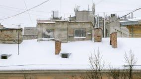 Tubo que fuma Chimenea en el tejado nevoso en de la casa en un día de invierno frío, época en que la calefacción se enciende almacen de metraje de vídeo