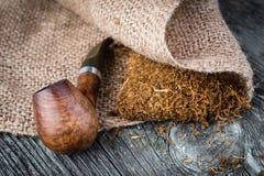 Tubo que fuma y tabaco en la arpillera Imagenes de archivo