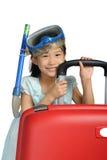 Tubo respirador que lleva y máscara de la pequeña muchacha asiática cerca de un rojo grande del viaje Imagen de archivo libre de regalías