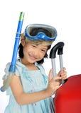 Tubo respirador que lleva y máscara de la pequeña muchacha asiática cerca de un rojo grande del viaje Fotos de archivo