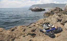 Tubo respirador y chancletas en la playa de piedra fotos de archivo