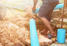 Tubo roto en agujero con el movimiento del agua en la reparación de trabajo del borde de la carretera y del fontanero foto de archivo libre de regalías