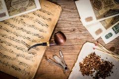 Tubo, tabacco, vecchi soldi e note Fotografia Stock Libera da Diritti