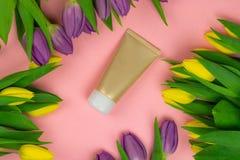 Tubo vac?o de la crema en un fondo rosado con las flores imagen de archivo libre de regalías