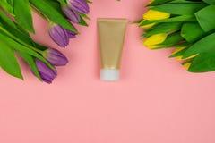 Tubo vac?o de la crema en un fondo rosado con las flores imagen de archivo