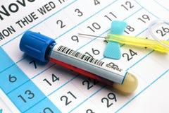 Tubo y aguja de la sangre sobre un calendario de cita en el banco de trabajo o Imagen de archivo