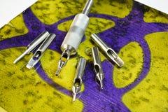 Tubo y extremidades del tatuaje del acero inoxidable con la advertencia Foto de archivo