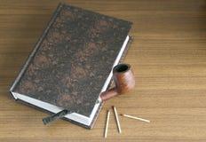 Tubo y libro Foto de archivo libre de regalías