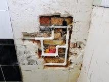 Tubo y puertas del propileno en una pared de ladrillo - soldadura del propileno foto de archivo